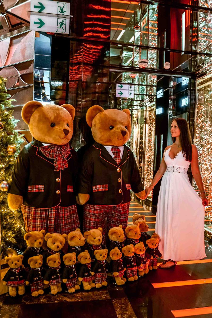 Girl in a white dress holding hands with a stuffed bear which is a part of the Christmas decoration