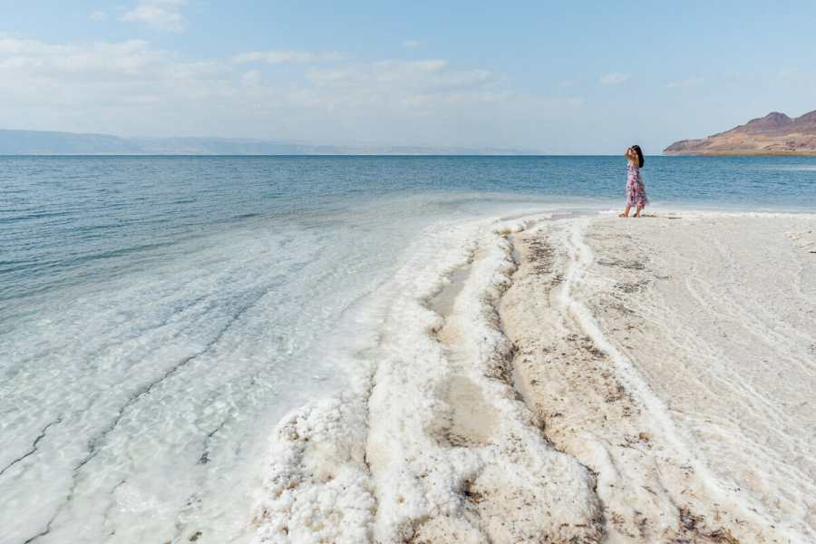 Girl in a pink floral dress standing on the white salt formations at the Dead Sea in Jordan