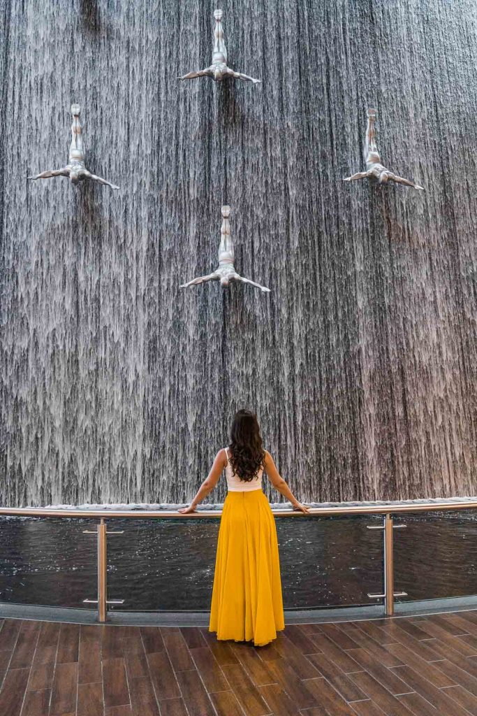 Girl in yellow skirt standing in front of the Waterfall Wall in the Dubai Mall