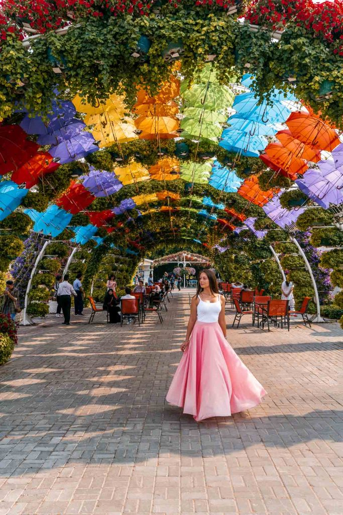 Girl in a pink skirt standing under colorful umbrellas in the Dubai Miracle Garden