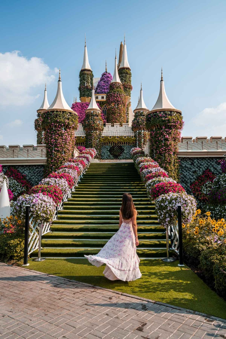 Girl in pink floral dress standing in front of a castle made of flowers in the Dubai MIracle Garden