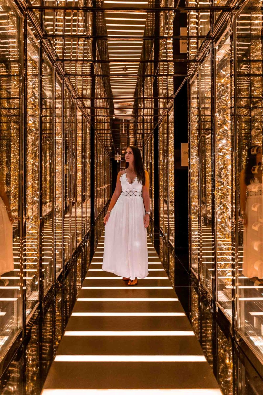 Girl in white dress standing in the middle of a golden corridor