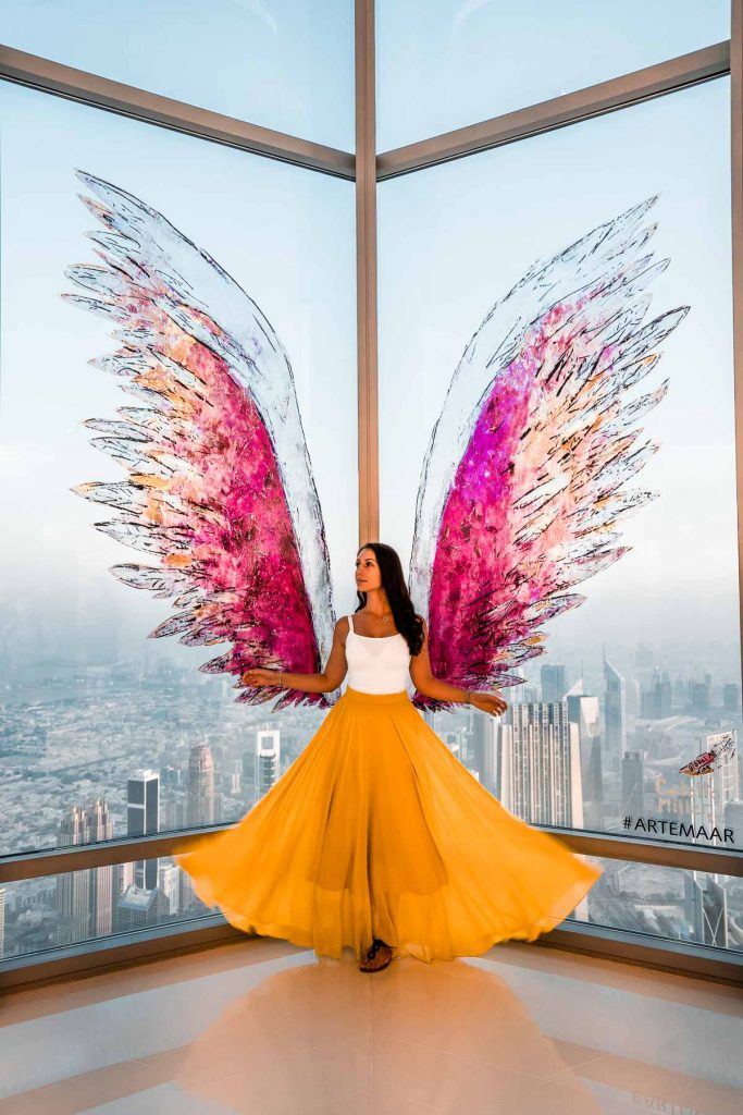 Girl in a yellow skirt standing in front of a pink instagrammable wing at the Burj Khalifa in Dubai