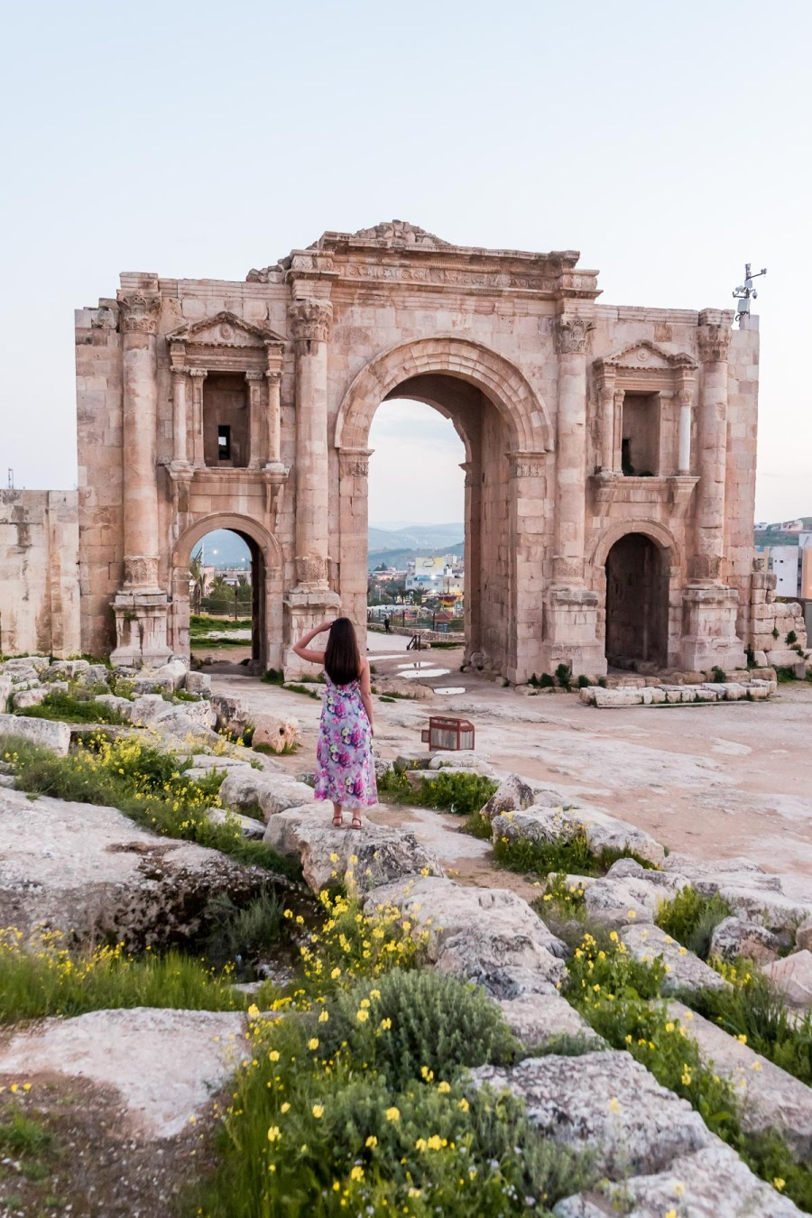 Girl in a purple floral dress standing in front of the ruins of Jerash in Jordan