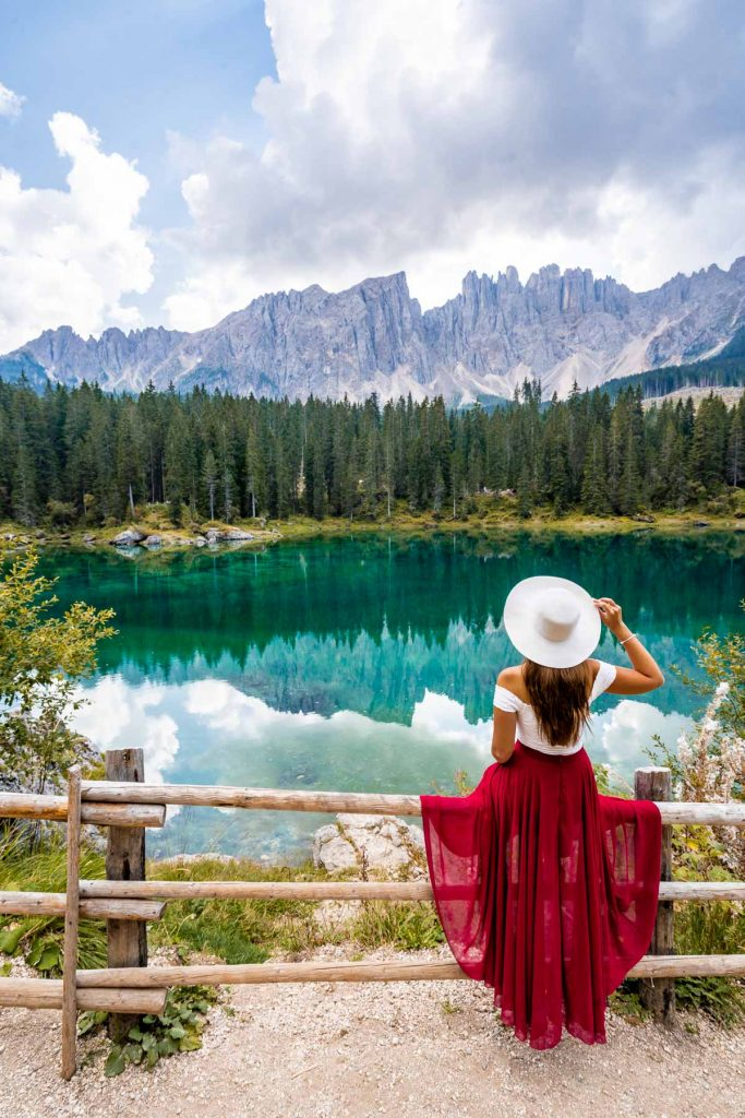 Girl in a red skirt sitting on the fence at Lago di Carezza, which is a must stop on every Dolomites road trip