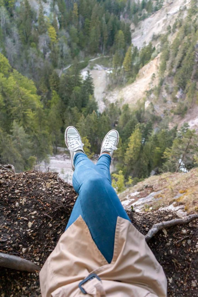 Girl sitting at the edge of a cliff, looking down at the gap