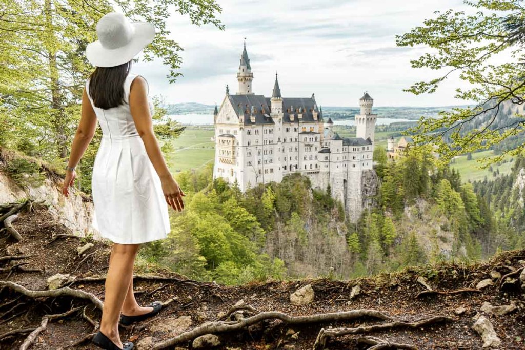 Girl in a white dress standing at the secret viewpoint at Neuschwanstein Castle