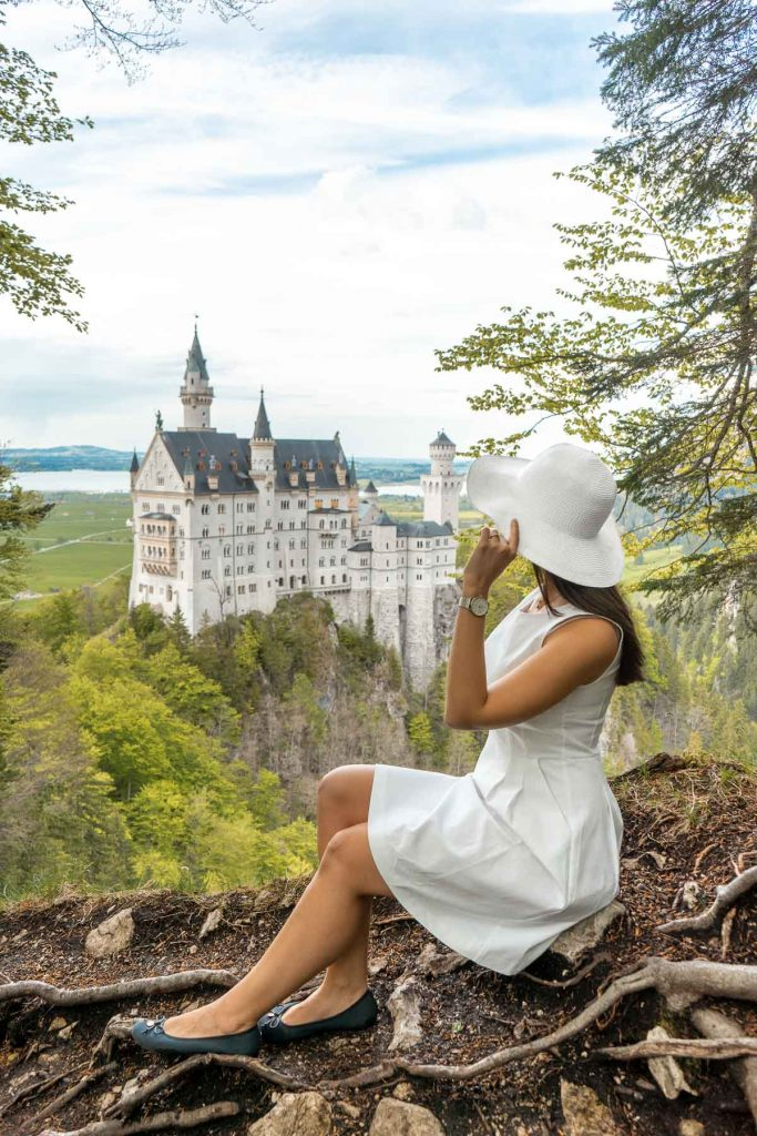 Girl in a white dress sitting at the secret viewpoint at Neuschwanstein Castle