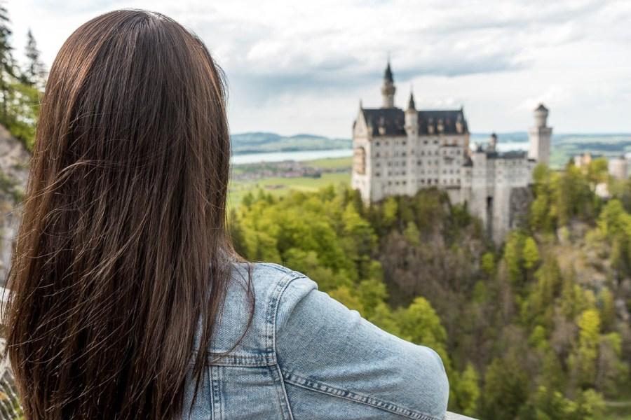 Girl in a denim jacket looking at the Neuschwanstein Castle from the Marienbrücke