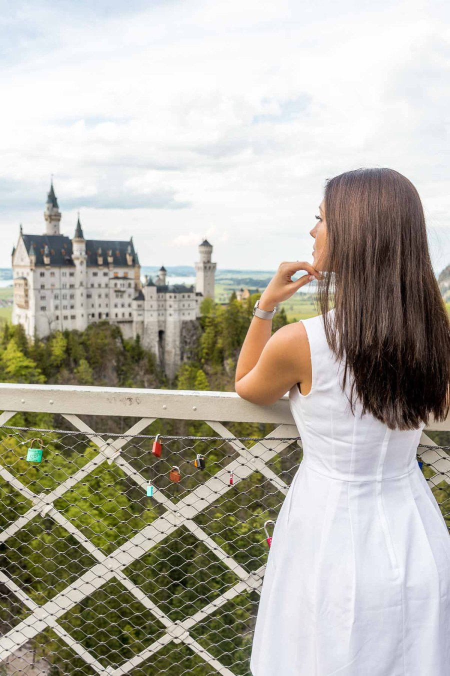 Girl in a white dress looking at the Neuschwanstein Castle from the Marienbrücke