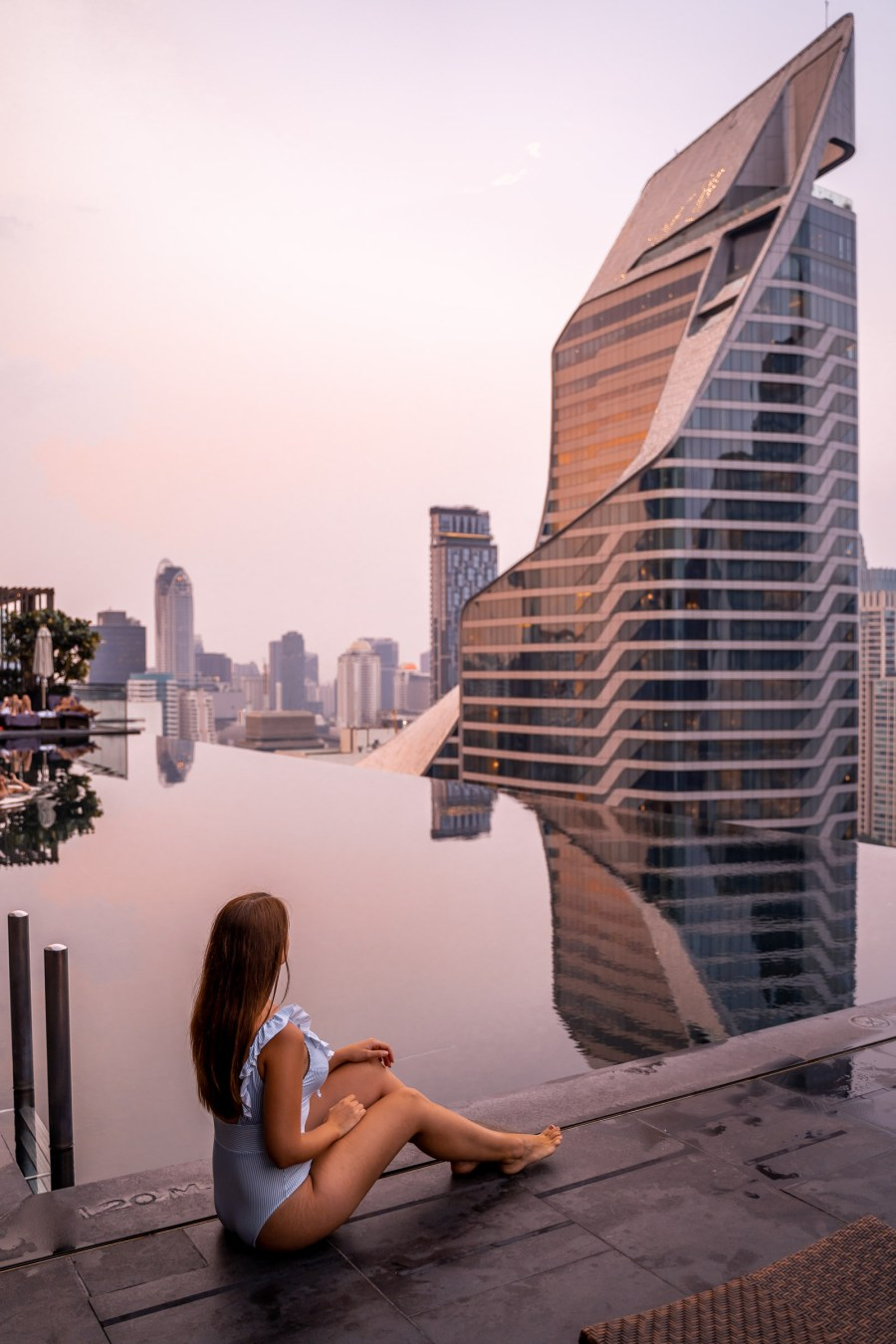 Girl in a blue swimsuit sitting in front of the infinity pool at the Okura Prestige Bangkok watching the sunset with the Bangkok skyline in the background