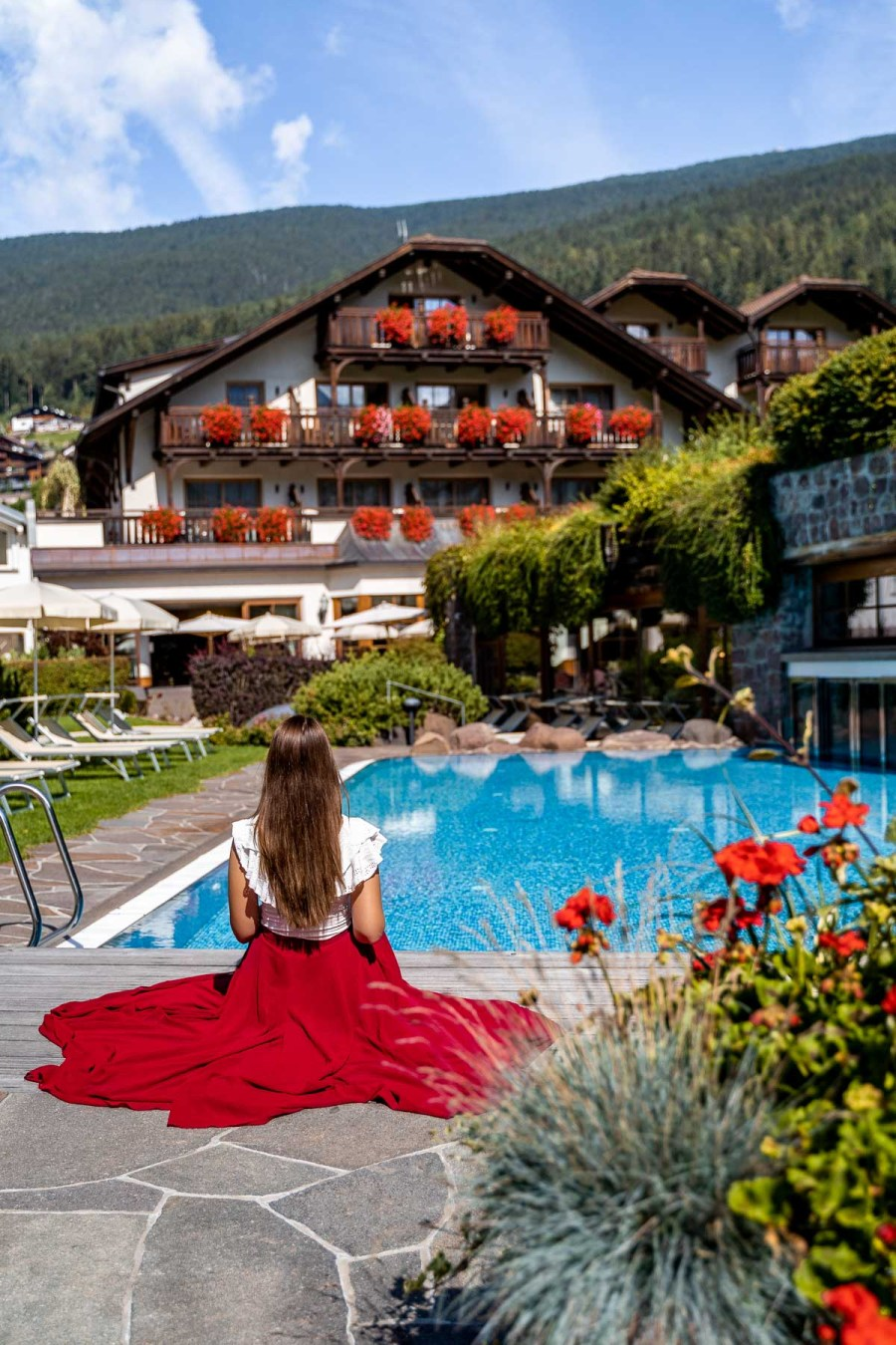 Girl in a red skirt sitting in front of the pool at Hotel Angelo Engel in Ortisei, Dolomites