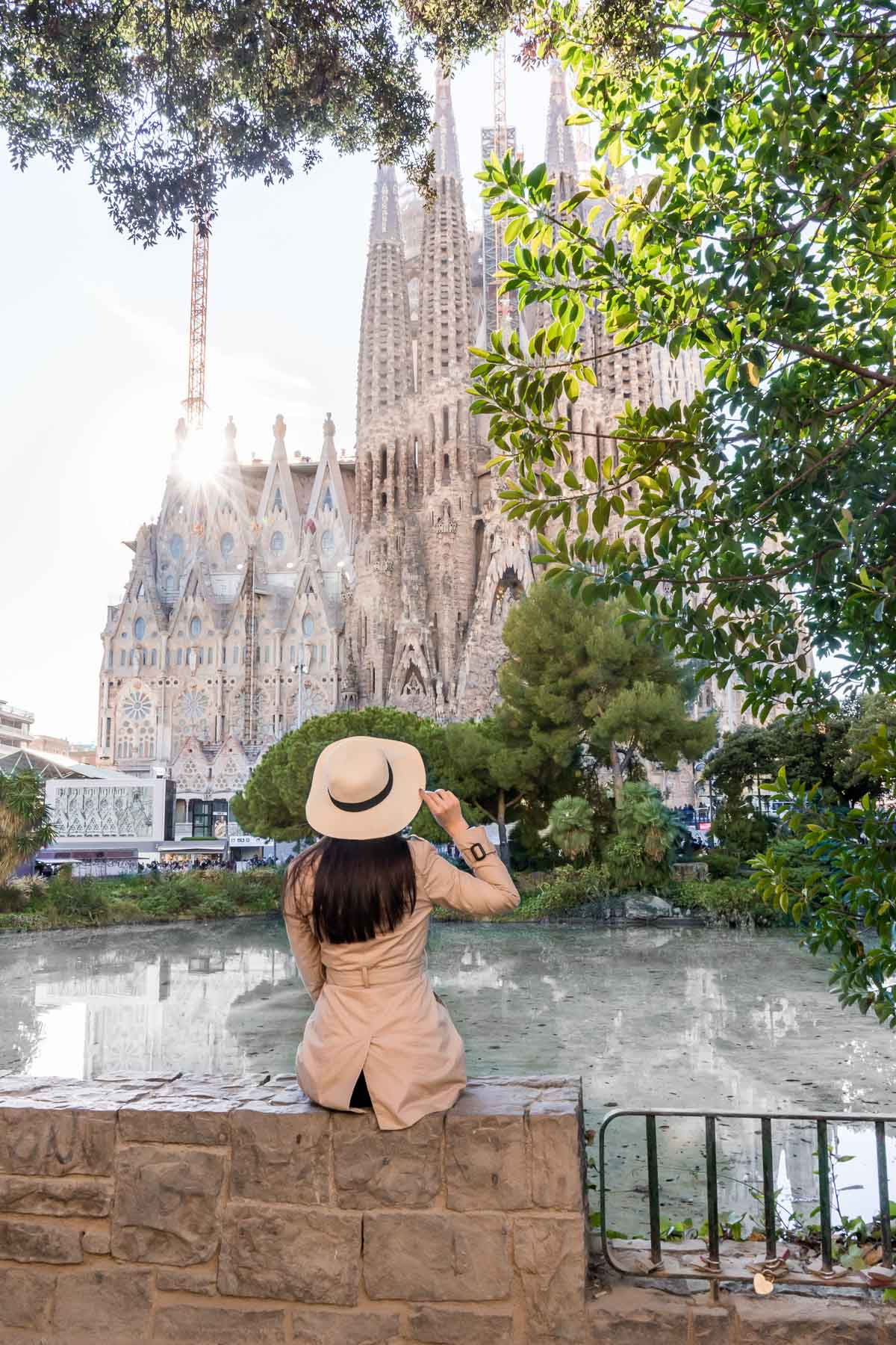 Girl in a hat and a trench coat sitting in front of the Sagrada Familia in Barcelona