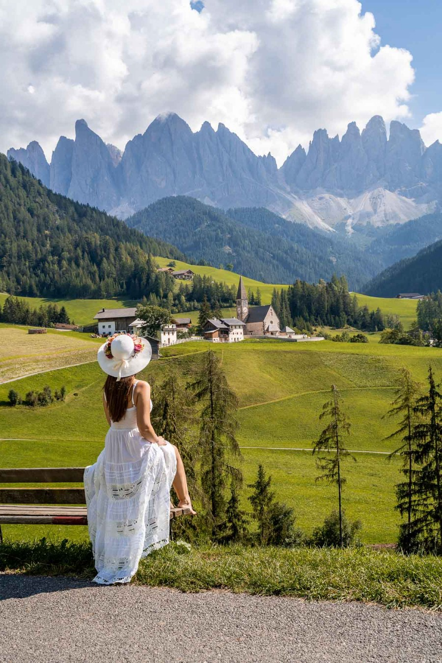 Girl in a white dress sitting on a bench, looking at Santa Maddalena church in Val di Funes, which is a most visit on a Dolomites road trip