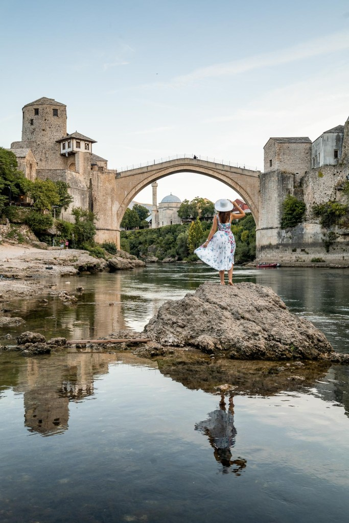 Girl in a floral dress standing on a rock in front of the Stari Most Old Bridge in Mostar, Bosnia-Herzegovina
