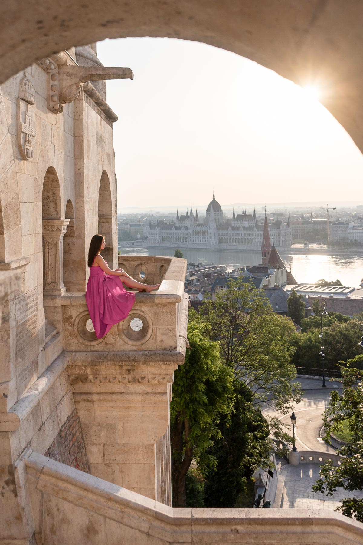 Girl in pink dress sitting at the edge of the Fisherman's Bastion in Budapest with the Hungarian Parliament in the background