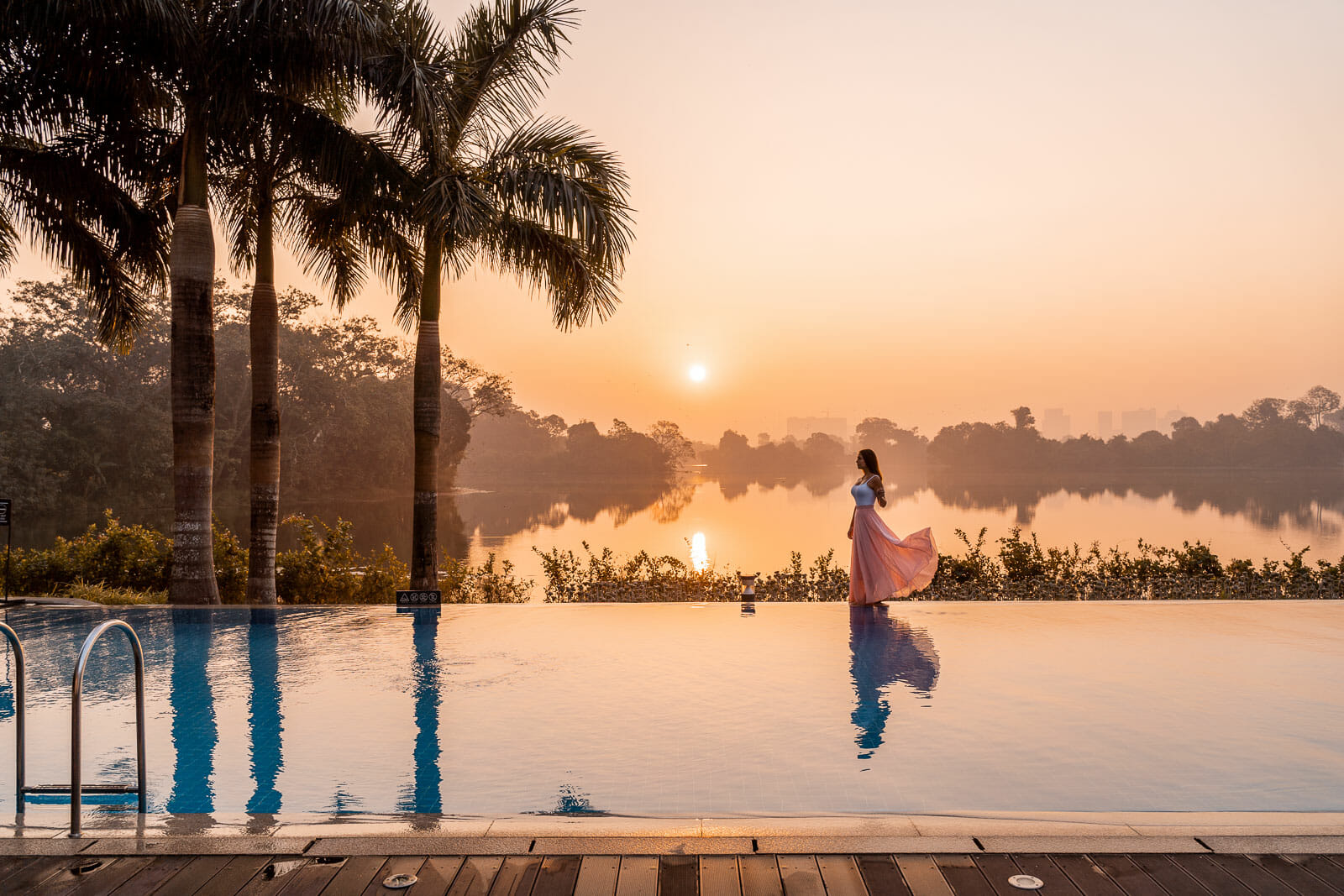 Girl in a pink skirt standing at the edge of the pool at Lotte Hotel Yangon looking at the sunrise
