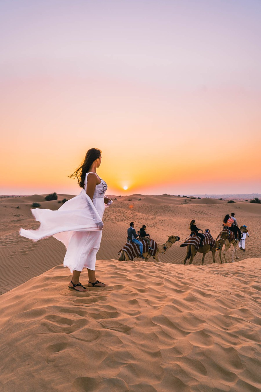 Sunset view in the Dubai desert with a girl in white dress standing in the sand dunes