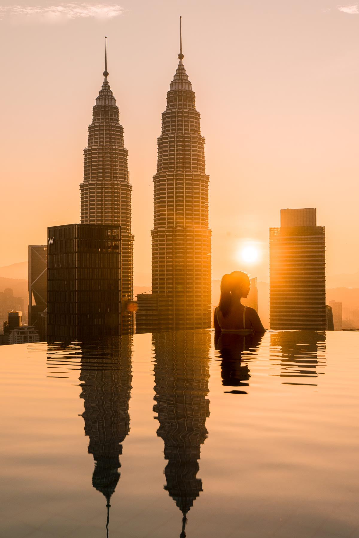 The silhouette of a girl in an infinity pool overlooking the Petronas Towers in Kuala Lumpur at sunrise