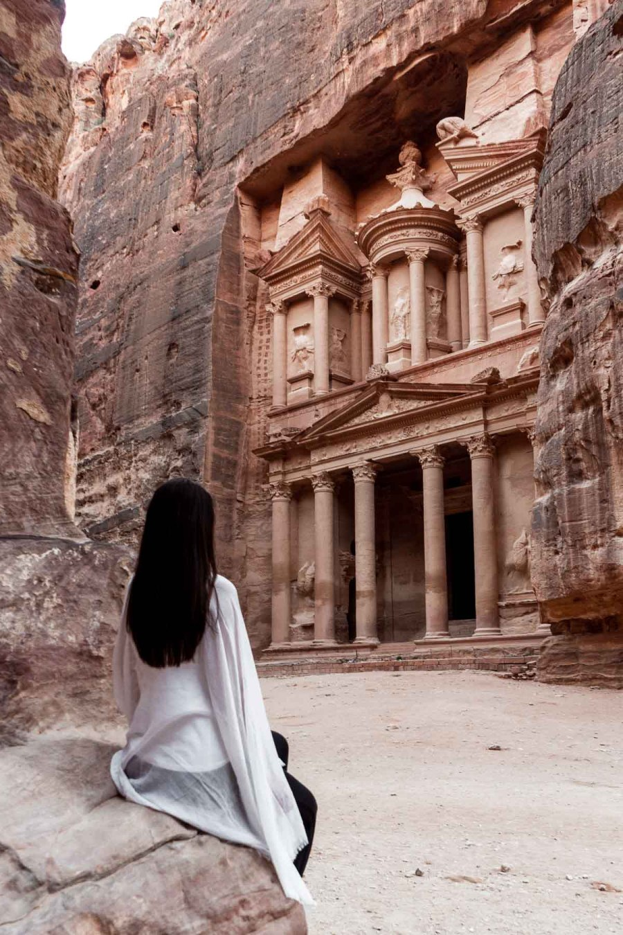 Girl in a white scarf looking at the Treasury in Petra, Jordan