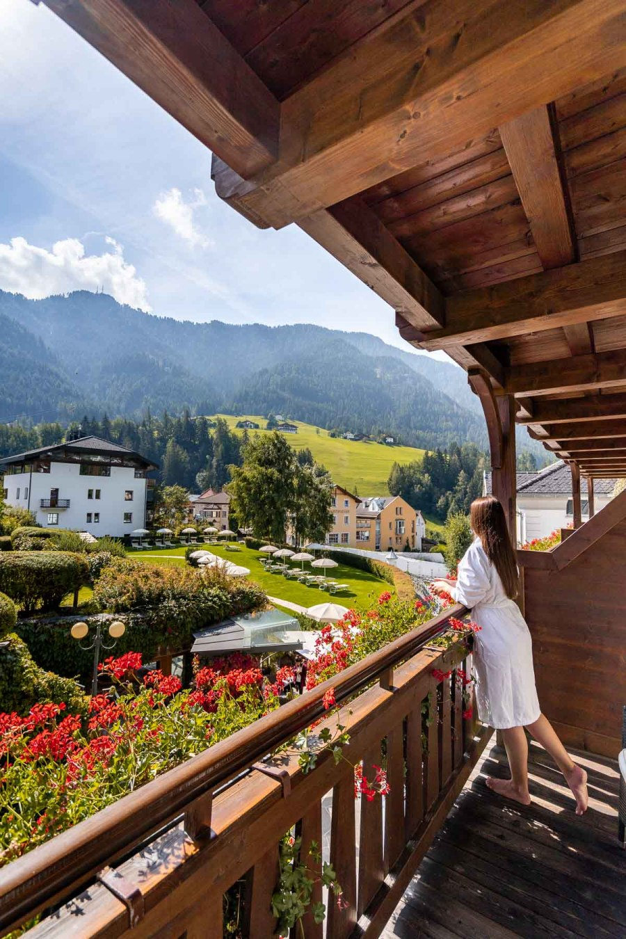 Girl in a bathrobe looking at the view from the room at Hotel Angelo Engel in Ortisei, Dolomites