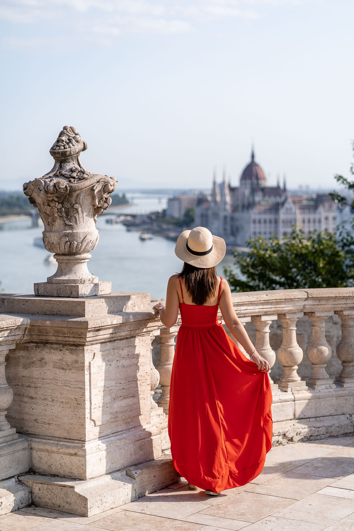 Girl in a red dress standing at the Buda Castle with the Hungarian Parliament in the background
