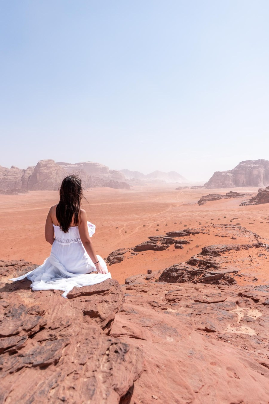 Girl in a white dress looking at the view in the Wadi Rum, Jordan