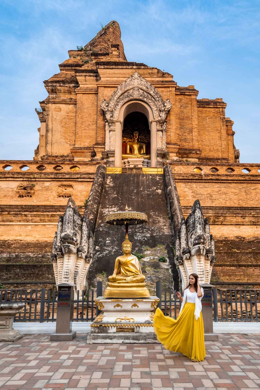 Girl in a yellow skirt in front of the Wat Chedi Luang Temple in Chiang Mai