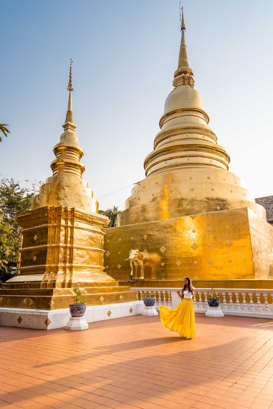 Girl in a yellow skirt in front of the golden stupas at Wat Phra Singh Temple in Chiang Mai