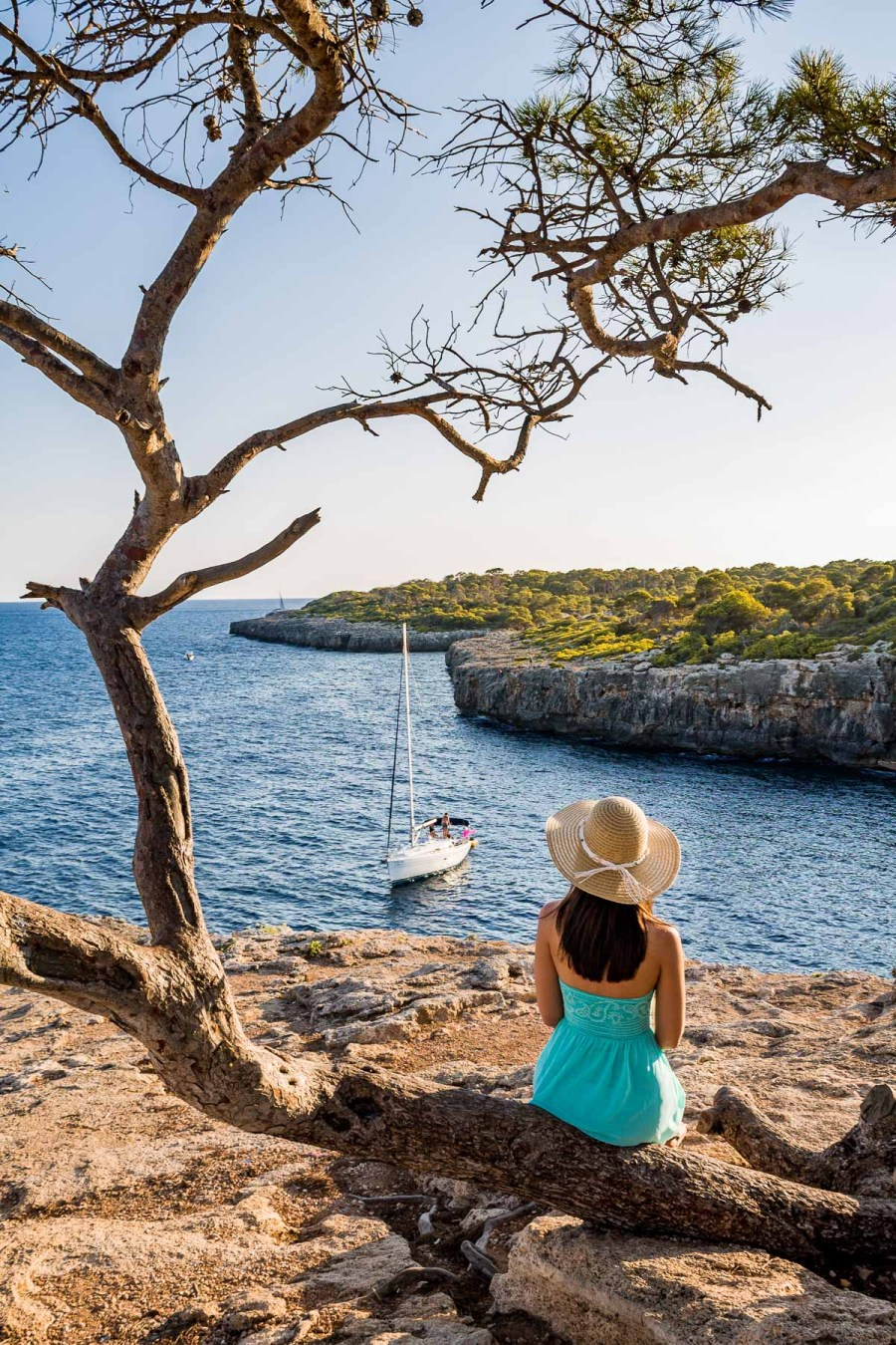 Girl in a blue dress sitting on a tree at Cala Pi in Mallorca