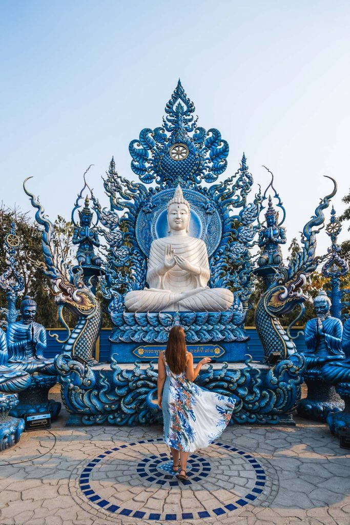 Girl in a blue dress standing in front of a white Buddha statue at the Blue Temple in Chiang Rai