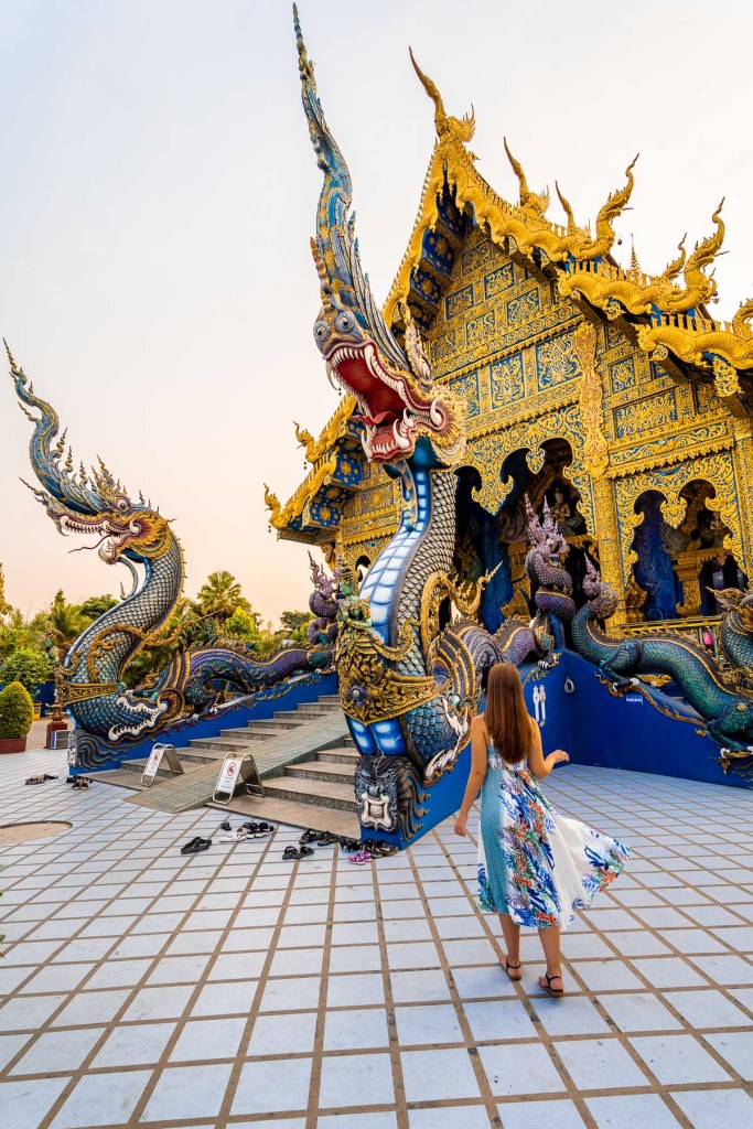 Girl in a blue dress standing in front of the Blue Temple in Chiang Rai