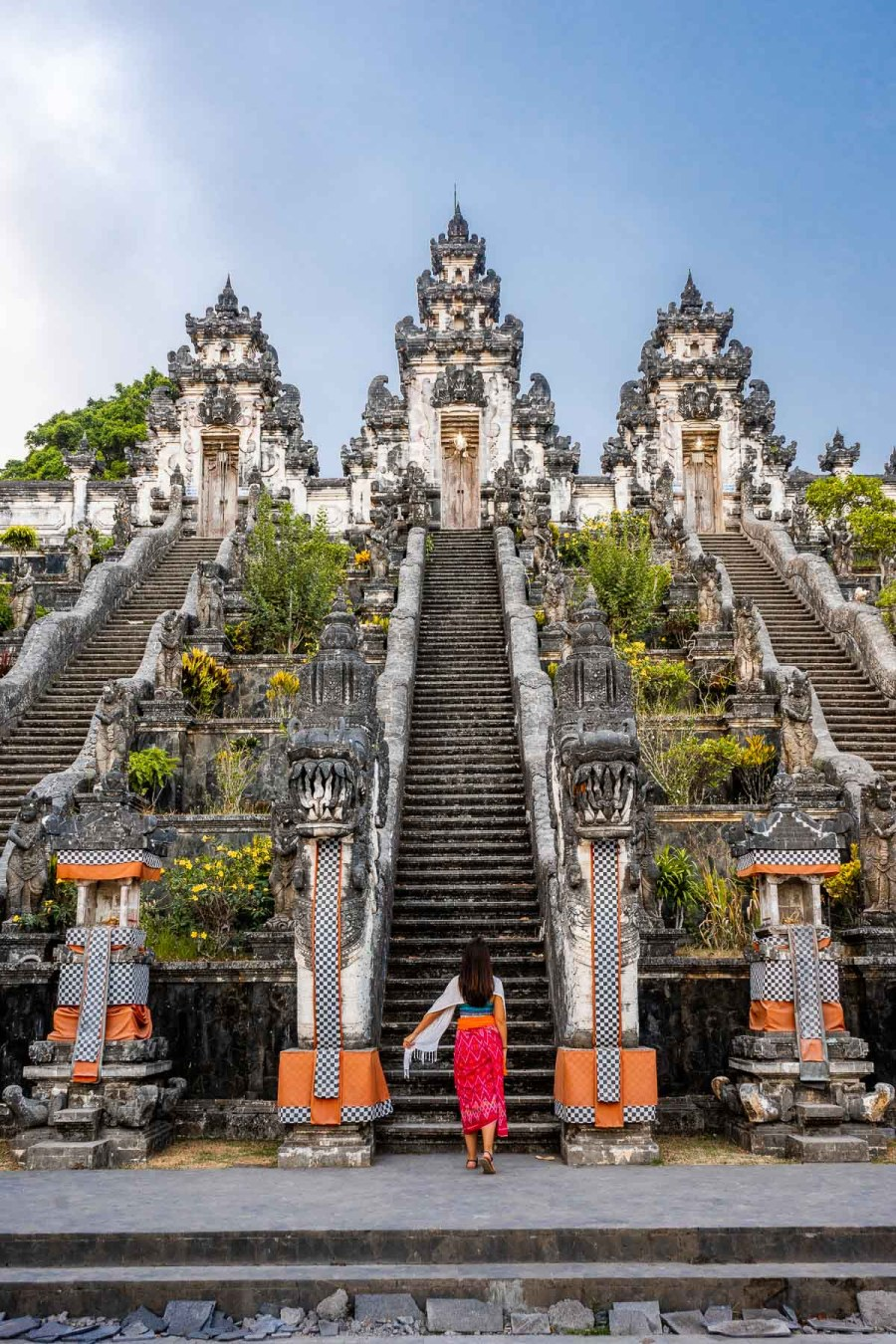 Girl in a pink sarong standing in front of Pura Lempuyang Temple in Bali