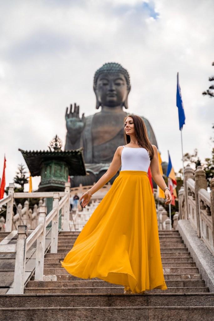 Girl in a yellow skirt standing in front of Tian Tan Buddha in Hong Kong