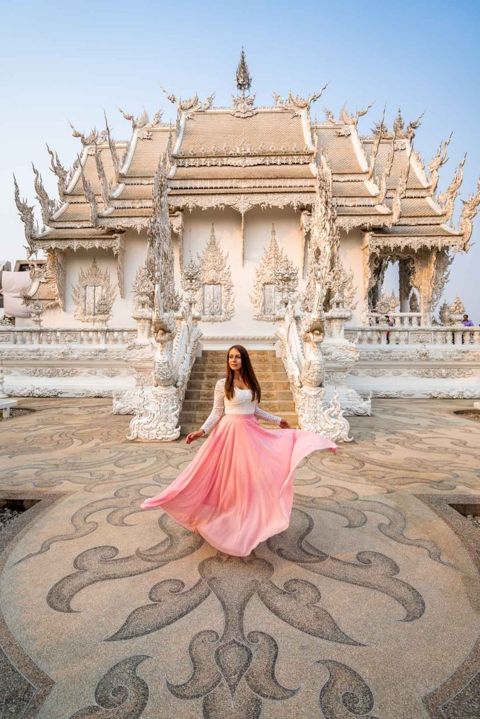 Girl in a pink skirt twirling in front of Wat Rong Khun, the White Temple in Chiang Rai