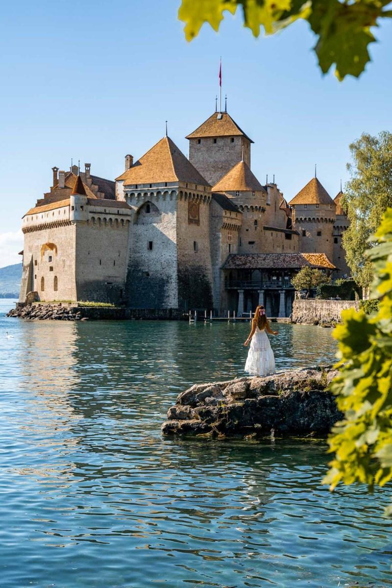 Girl in a white skirt in front of Chillon Castle, Switzerland