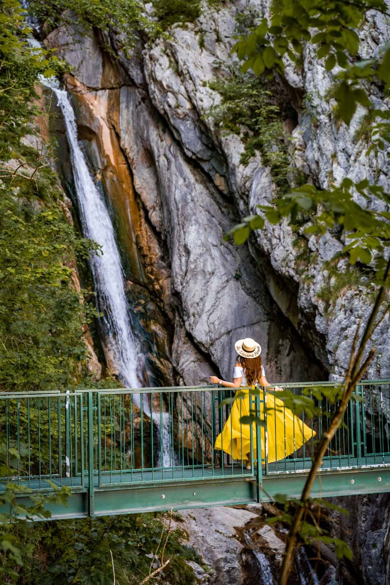 Girl in a yellow dress in front of Hallstatt Waterfall