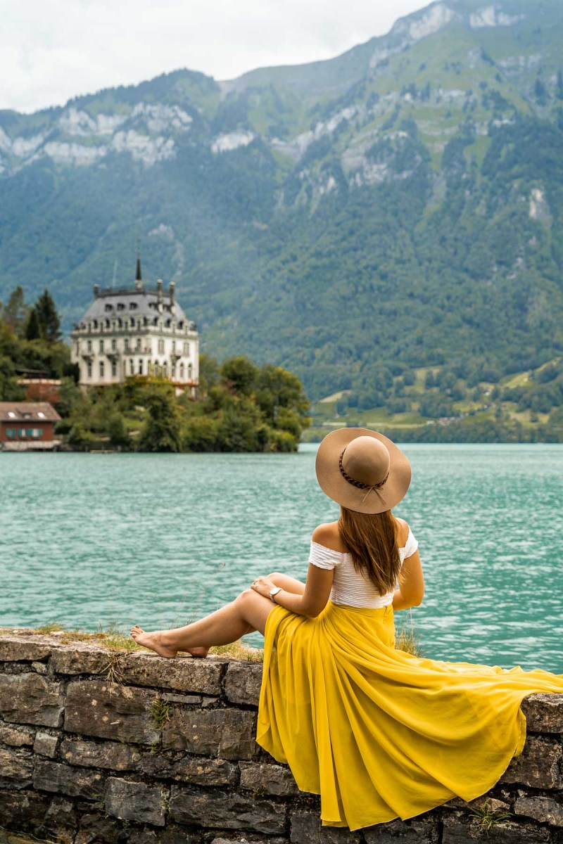 Girl in a yellow skirt sitting in front of Schloss Seeburg at Lake Brienz