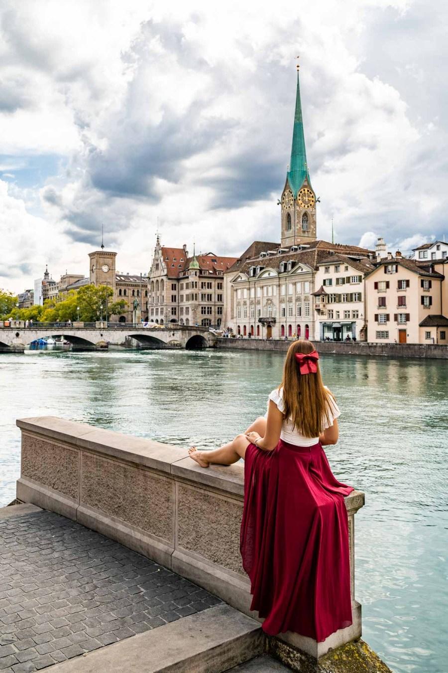 Girl in a red skirt sitting by the riverwalk in Zurich, Switzerland