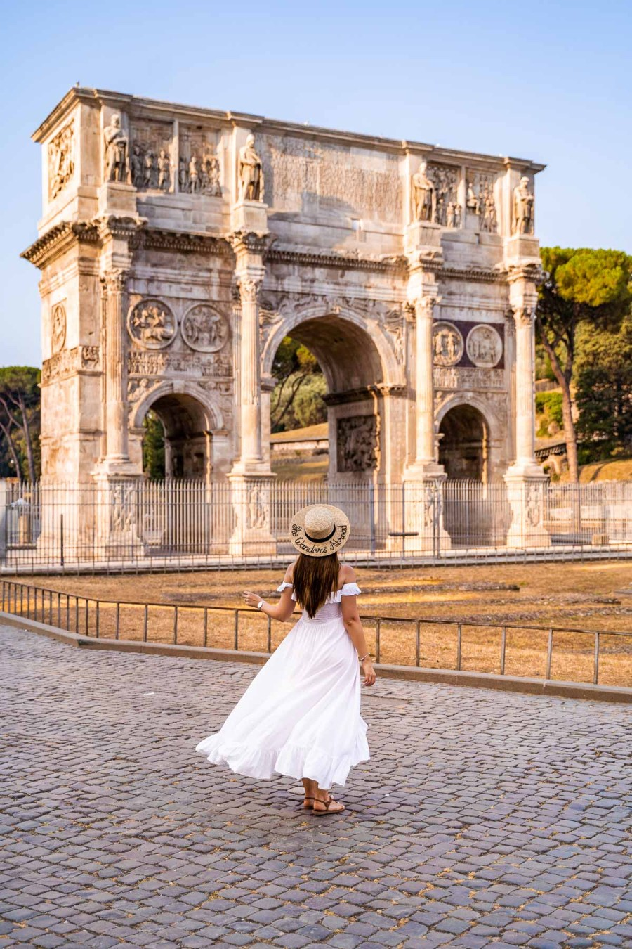Girl in a white dress in front of Arch of Constantine in Rome, Italy
