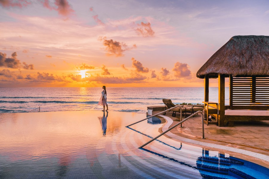 Girl walking on the edge of an infinity pool at sunrise at JW Marriott Cancun