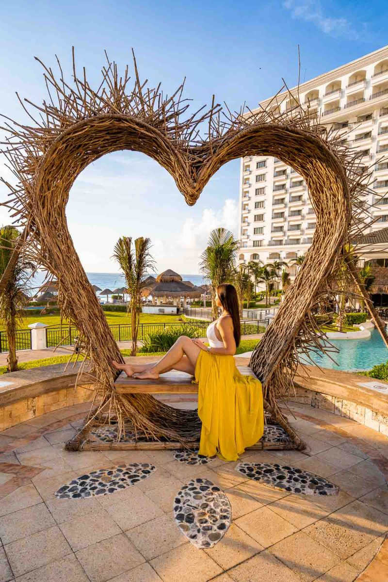 Girl in a yellow skirt sitting in a wooden heart at JW Marriott Cancun