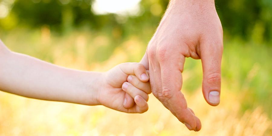 Сын держится за мизинец отцовской руки