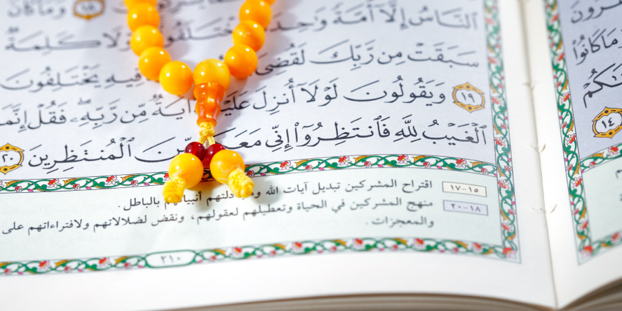 Жёлтые чётки на открытом Коране