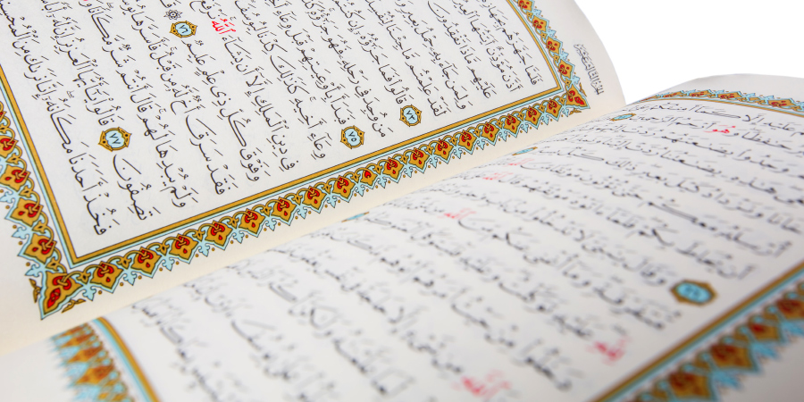 Открытый Коран на белом фоне