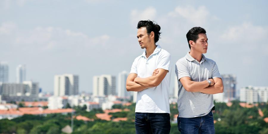 Два недовольных азиата стоят рядом, отвернувшись друг от друга
