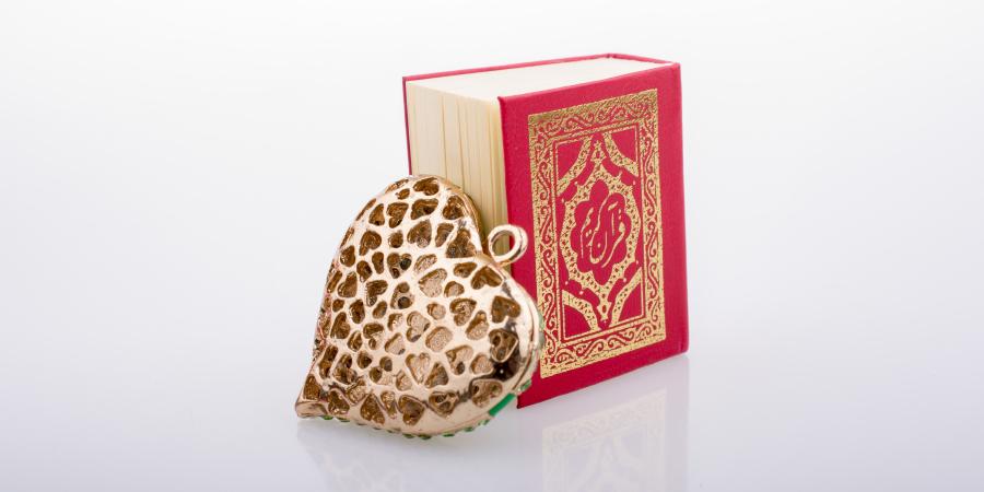 Золотое украшение в виде сердца и миниатюрный Коран