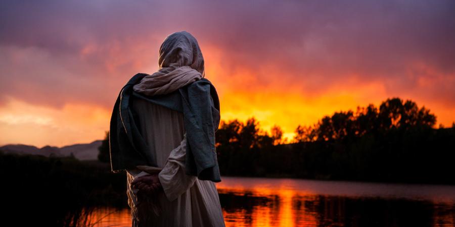 Человек в белом капюшоне смотрит на закат, стоя у озера