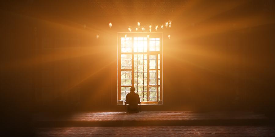 Человек, сидящий возле окна мечети
