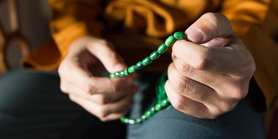 Мужчина, перебирающий зелёные чётки